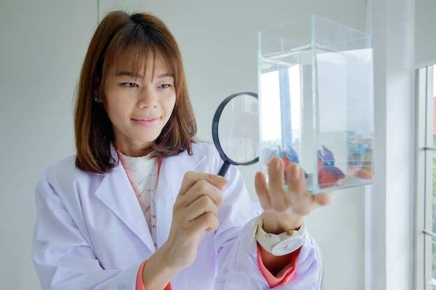 Woman doctor hold magnifying glass looking fish in tank Premium Photo