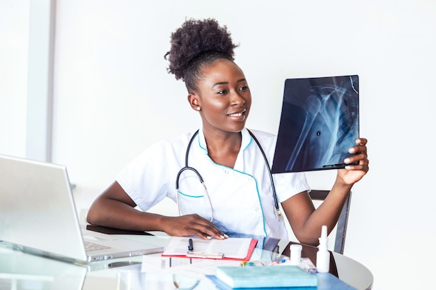 Woman doctor in hospital looking at x-ray film healthcare, roentgen, people and medicine concept. young smiling female doctor with stethoscope pointing at x-ray at doctor's office Premium Photo