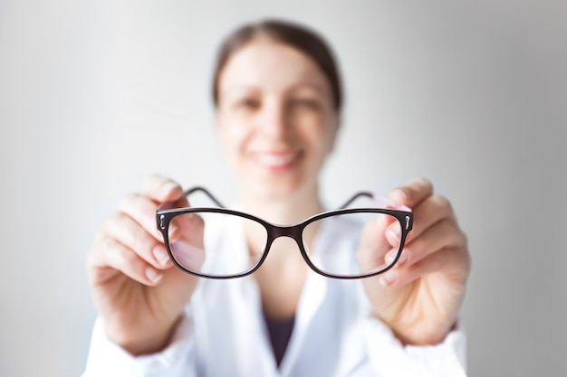 Woman doctor ophthalmologist is holding glasses. the concept of vision problems. optics for eyes. Premium Photo