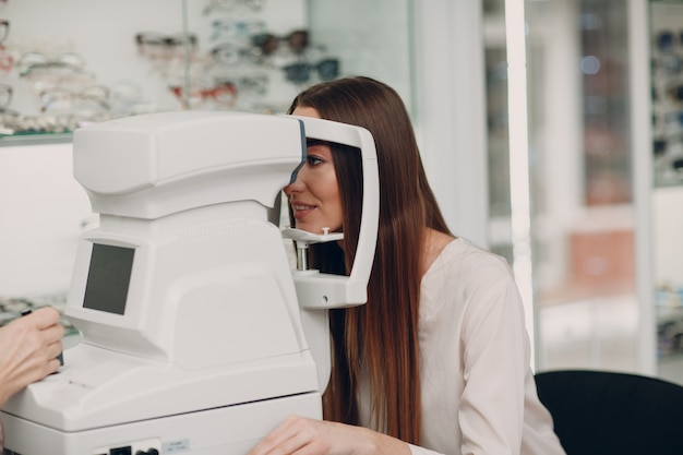 A woman doctor and patient doing opthalmology check vision test by refractometer Premium Photo