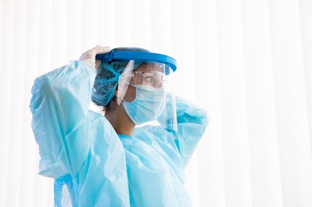Женщина-врач надевает свое пандемическое оборудование Premium Фотографии