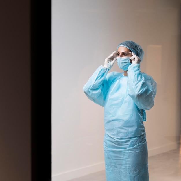 Женщина-врач надевает маску для лица Premium Фотографии