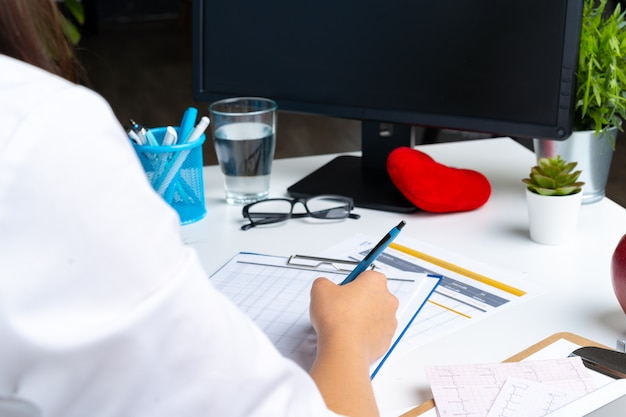 Woman doctor taking notes on clipboard while sitting at her table in office Premium Photo
