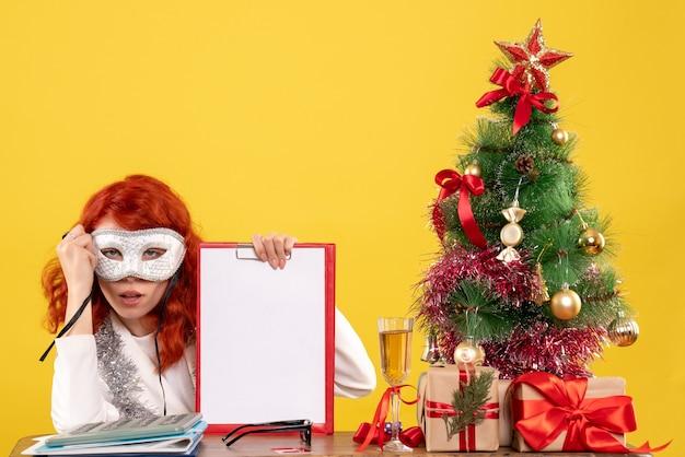 クリスマスツリーの周りにマスクを身に着けている女性医師と黄色のプレゼント 無料写真