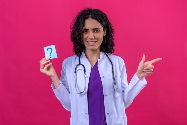 Женщина-врач в белом халате со стетоскопом, держащая напоминание с вопросительным знаком, очень счастлива, указывая пальцем в сторону на изолированном розовом Бесплатные Фотографии