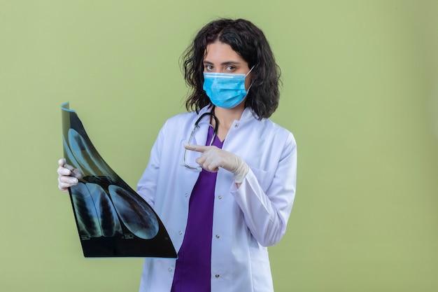 Женщина-врач в белом халате со стетоскопом в медицинской защитной маске держит рентген легких, указывая на него пальцем с серьезным лицом на изолированном зеленом Бесплатные Фотографии