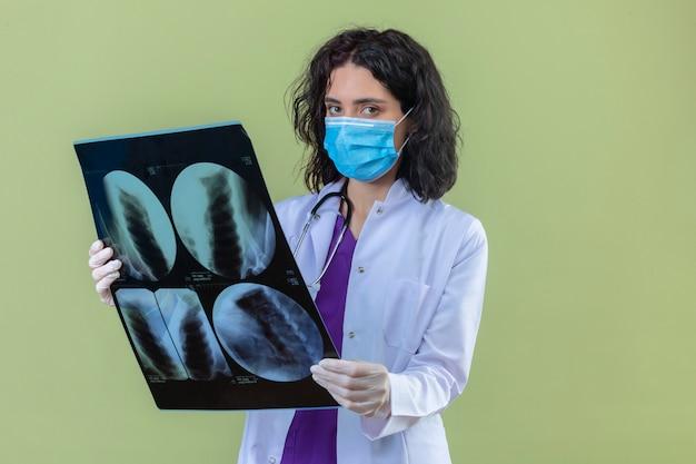 Женщина-врач в белом халате со стетоскопом в медицинской защитной маске стоит с рентгеновским снимком легких с серьезным лицом на изолированном зеленом Бесплатные Фотографии