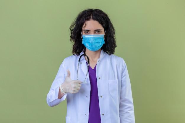 격리 된 녹색에 서 엄지 손가락을 보여주는 얼굴에 미소로 의료 보호 마스크에 청진 기 흰색 코트를 입고 여자 의사 무료 사진