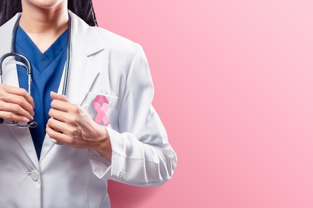 A woman doctor in a white lab coat holding a stethoscope on her hands with pink ribbon over pink background Premium Photo