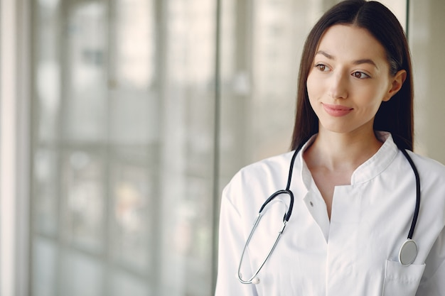 Woman doctor in a white uniform standing in a hall Free Photo