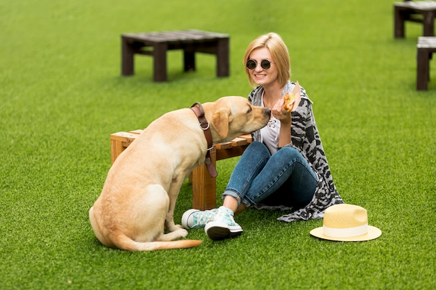 Woman and dog eating food in park Free Photo