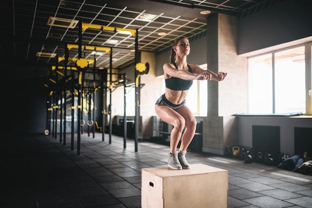 フィットネスクラブでボックスジャンプ運動をしている女性 Premium写真
