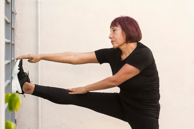 Woman doing cardio and leaning with a leg on wall Free Photo