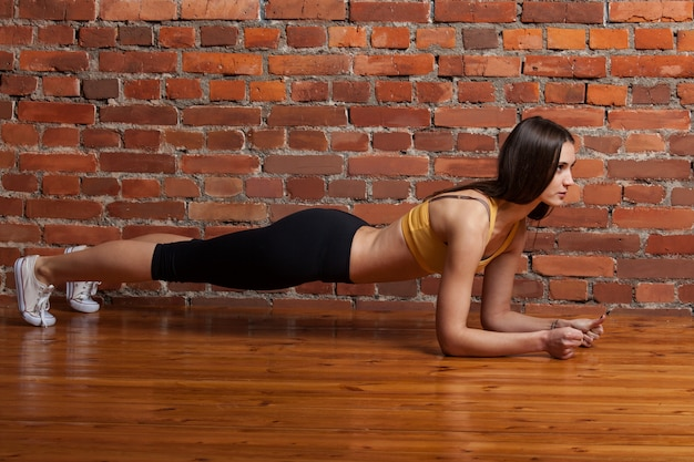 Woman doing exercise on a brick wall background Premium Photo