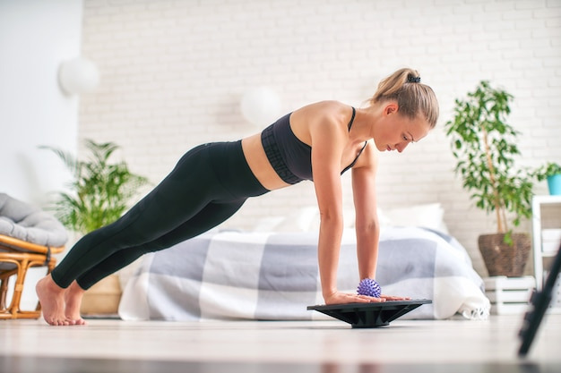 Woman doing exercise on a special simulator balancer. Premium Photo
