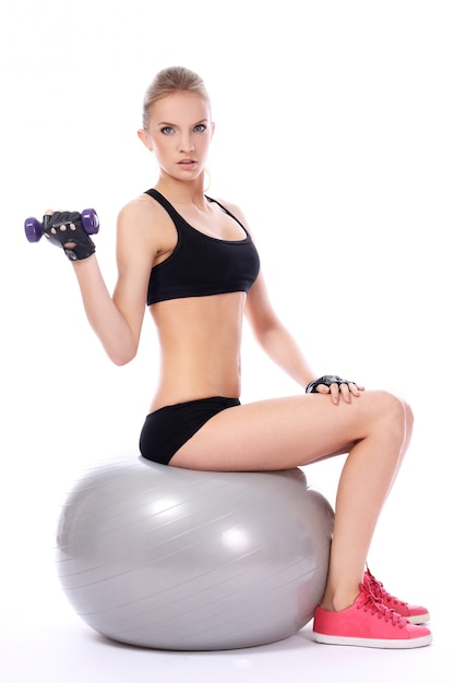 Woman doing exercises with dumbells on fitness ball Free Photo