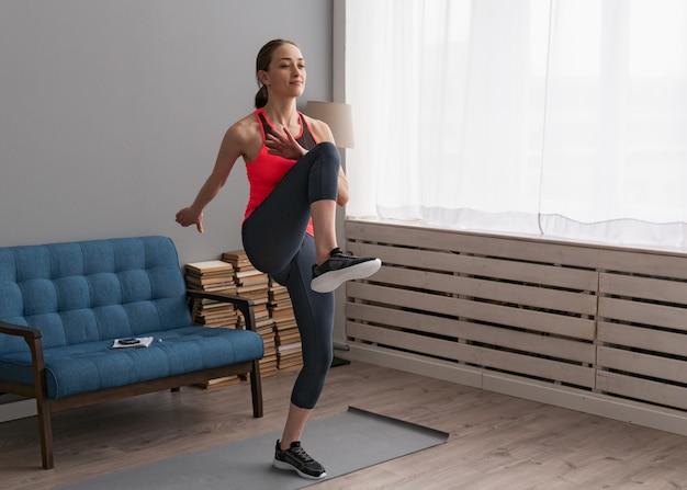 女性が自宅でフィットネストレーニングをして、高い膝を歩く Premium写真