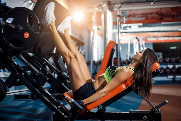 Woman doing fitness training on a leg extension push machine with weights Premium Photo