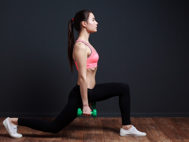 Woman doing frontal lunge squats with weight Premium Photo