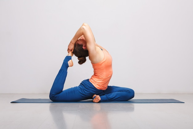 Woman doing hatha yoga asana eka pada rajakapotasana Premium Photo