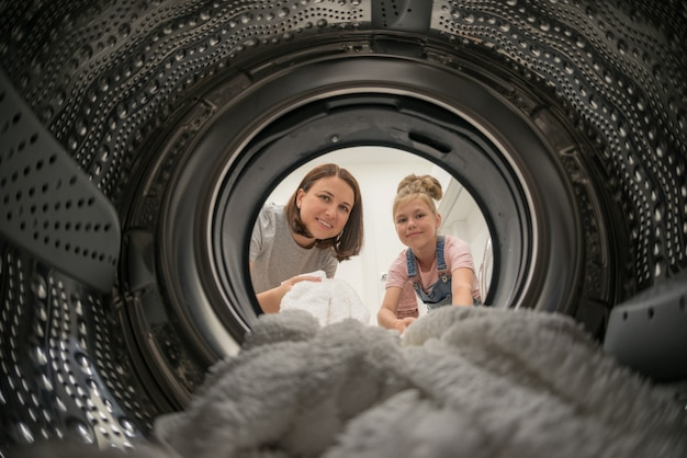 Woman doing laundry with her daughter reaching towel inside washing machine, view from inside Premium Photo