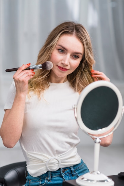 Woman doing makeup in front of mirror Free Photo