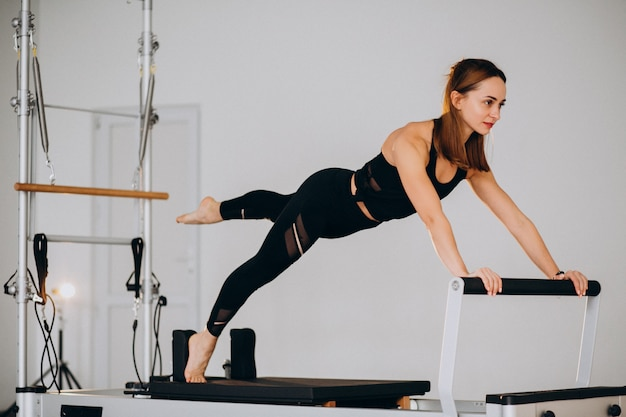 Woman doing pilates on a reformer Free Photo