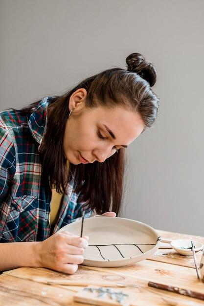 Donna che fa un capolavoro di ceramica Foto Gratuite
