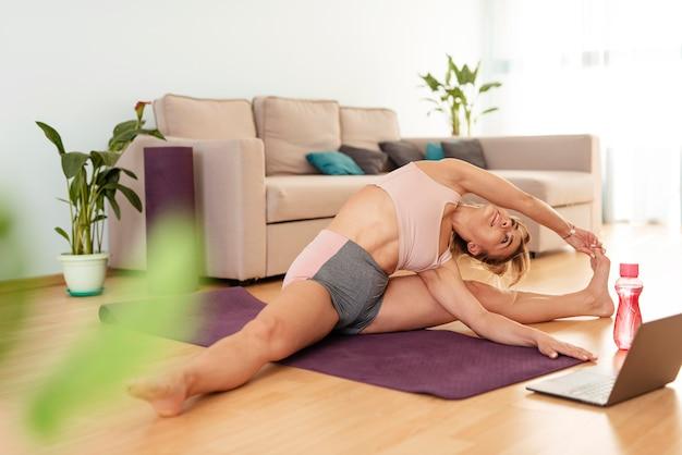 Женщина занимается спортом на дому Premium Фотографии