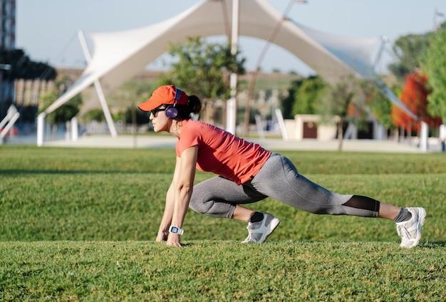 Женщина делает упражнения на растяжку, слушая музыку Premium Фотографии