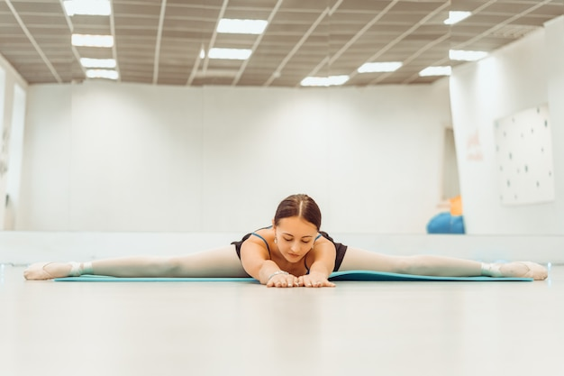 Woman doing stretching on the mat in the hall sitting on the twine Premium Photo