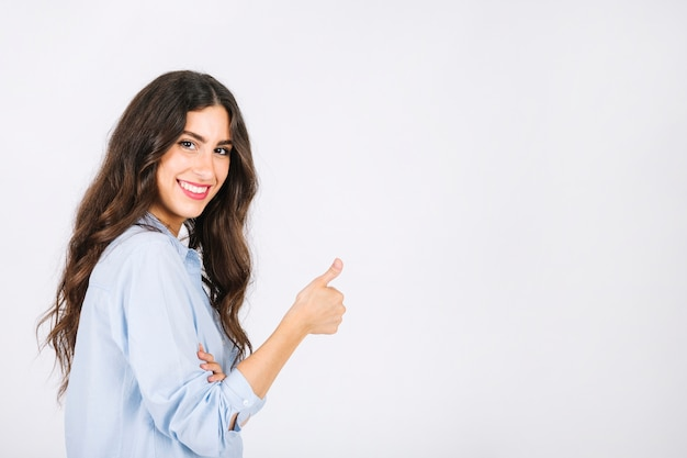 Woman doing thumbs up gesture towards copyspace Free Photo