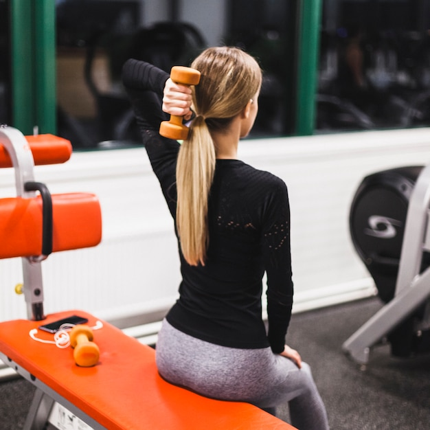 Woman doing triceps exercise with dumbbell Free Photo