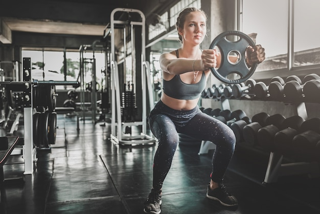 Woman doing workout with weight plate at the gym Premium Photo