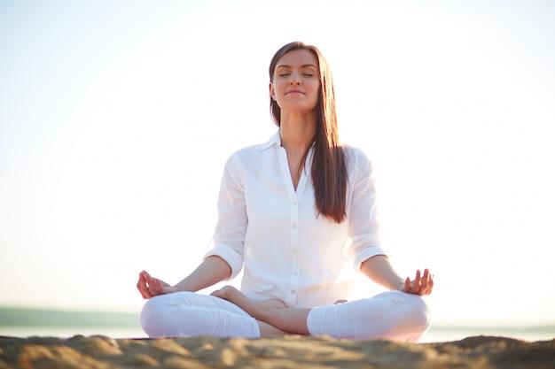 Woman doing yoga exercises on the beach Free Photo