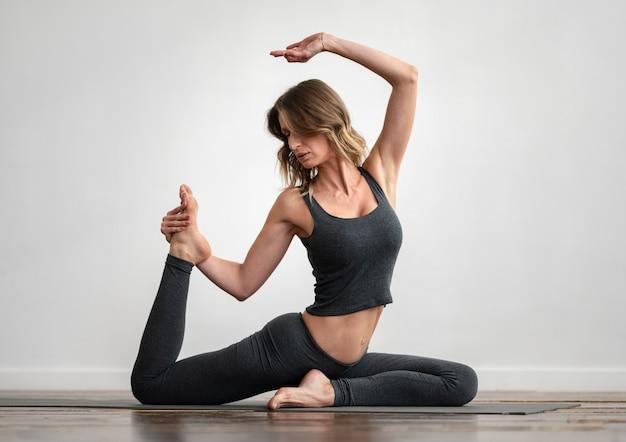 Donna che fa yoga a casa sulla stuoia Foto Gratuite