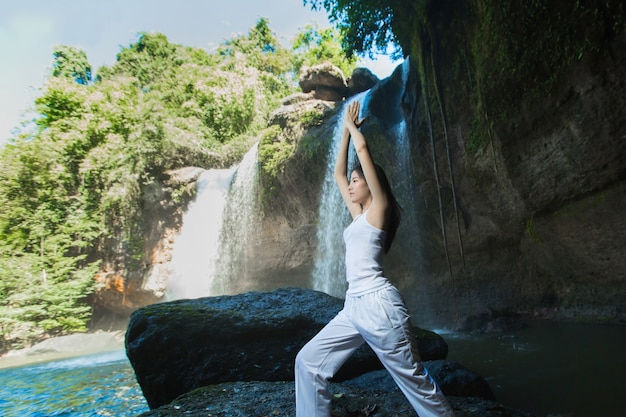 Woman doing yoga and meditation at the waterfall Premium Photo