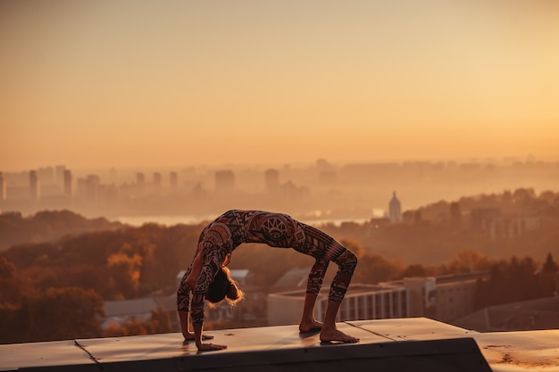 Woman doing yoga on the roof of a skyscraper in big city. Free Photo