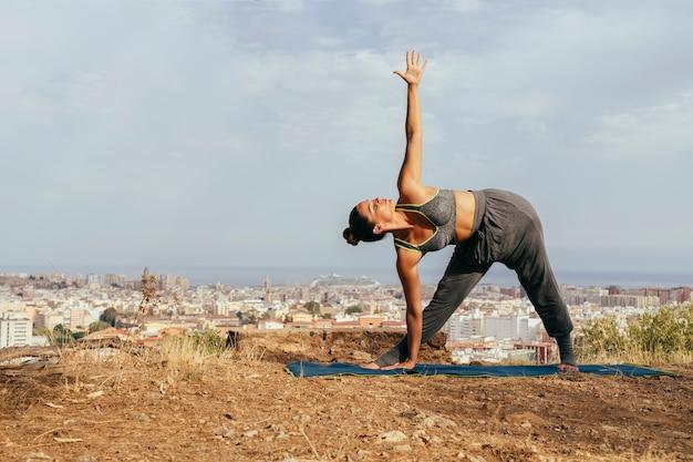 Donna che fa yoga con la città sullo sfondo Foto Gratuite