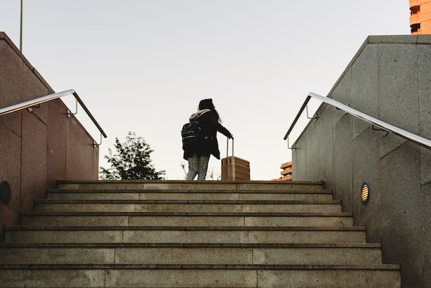 Woman dragging a trolley suitcase to climb the stairs of a subway. Premium Photo