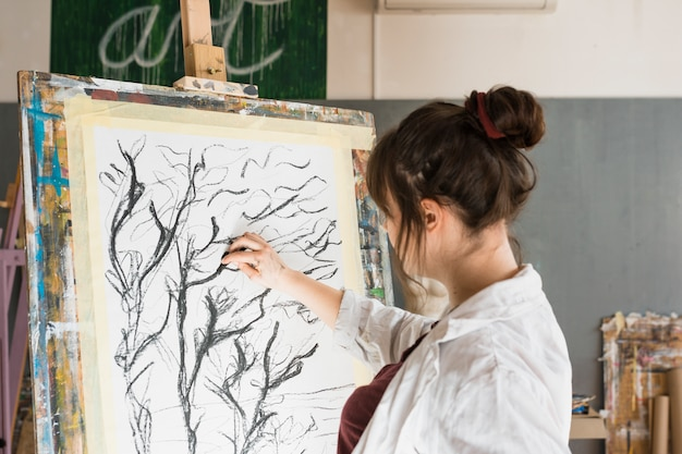 Woman drawing with charcoal on canvas at workshop Free Photo