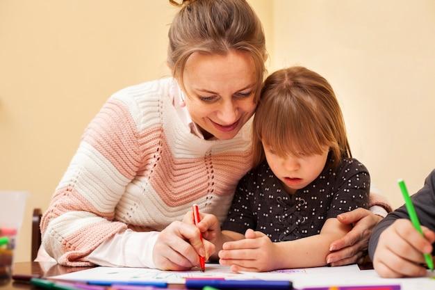 Женщина рисует с девушкой с синдромом дауна Бесплатные Фотографии