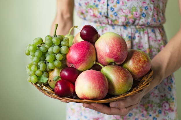 Woman in dress holds a basket with ripe fruits Premium Photo