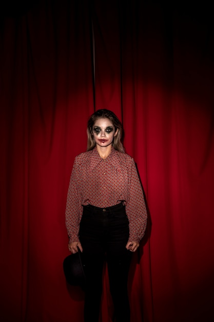 Woman dressed as a clown standing in front on a curtain Free Photo
