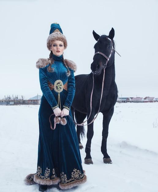 馬のある冬景色の美しいドレスに身を包んだ女性 Premium写真