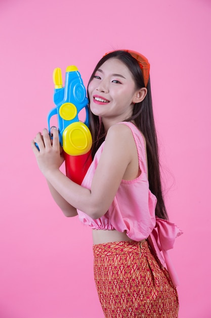 A woman dressed in a traditional thai folk clothes holding a water gun on a pink background. Free Photo