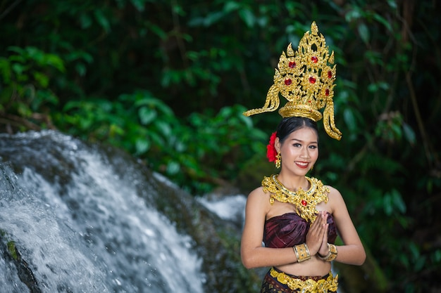 A woman dressed with an ancient thai dress at the waterfall. Free Photo