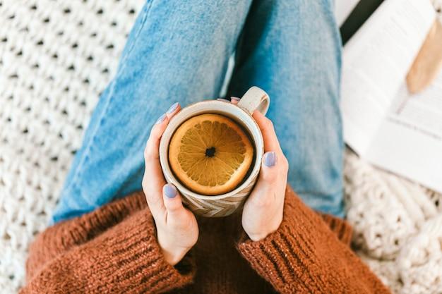 Женщина пьет чашку теплого травяного апельсинового чая Бесплатные Фотографии
