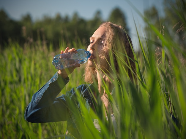 夏の暑い日に水のボトルを飲む女性 Premium写真