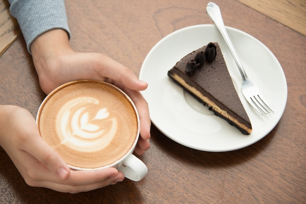 Woman drinking cappuccino and eating cake Free Photo